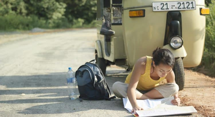 Young woman sitting on road reading map motor scooter in background